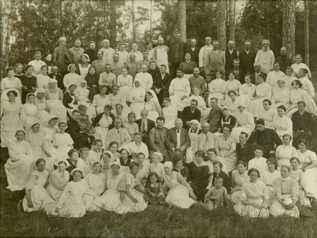 Rainis starp Bērnu slimnīcas darbiniekiem 1922. gadā. No Raiņa pa kreisi Andreja Priedkalna meita Marija un Priedkalns pats, pa labi nākamie LU profesori Pēteris Sniķers un Kārlis Barons. Rainim aiz muguras pa labi skaistā māsa Teofila Dambekalne, Priedkalnam aiz muguras pa kreisi – ārste Emīlija Cena. Attēlu muzejam 1977. gadā nodeva medicīnas māsa Alise Ziemele no Liepājas.